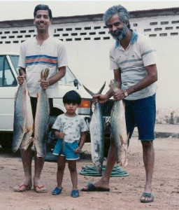 Michele holding a fish with his dad